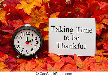 Some fall leaves and black and white alarm clock and white greeting card with text Taking time to be thankful