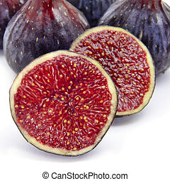 figs - some figs, one of them cut in half, on a white...
