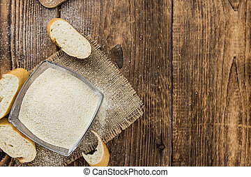 Some fresh Bread Crumbs on wooden background (selective ...