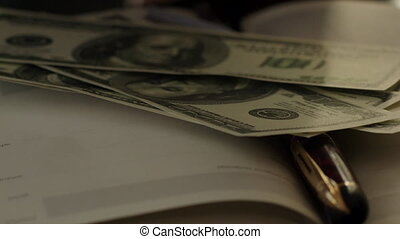 Some Hundred Dollars Banknotes on the Book
