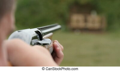 Some man aiming and shooting from a skeet shooting rifle in slow motion