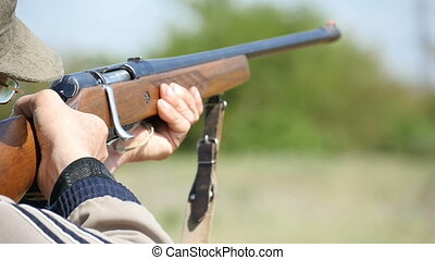 Some man aiming and shooting from a shotgun in a fieldin autumn  in slow motion