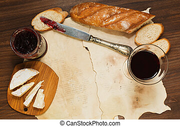 Some meal with red wine, bread, jam and cheese on oldened paper sheets