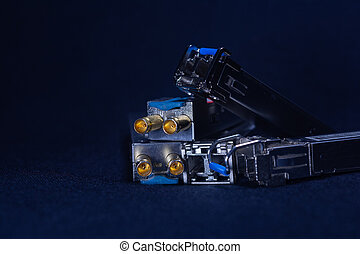 SOME OFC SFP SMALL FORM FACTOR PLUGGABLE ARE PLACED ON A BLACK BACKGROUND TELE COMMUNICATION 2