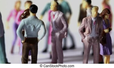 Some painted toy men and women stand in a jumble