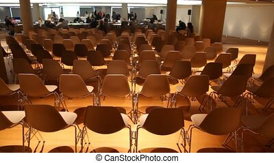 Some people move inside empty low light conference hall with many chairs