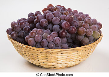 Some red grapes in a wooden pot over a white background