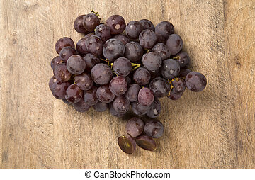 Some red grapes in a wooden pot over a wooden surface