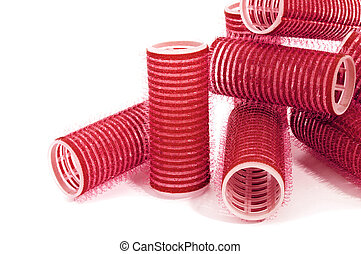 some red hair rollers on a white background