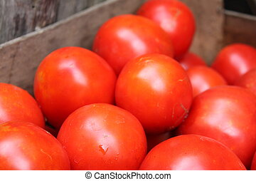 some red tomatoes in wooden box