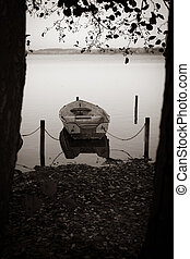 some rowboats lie at a lake in the north of Germany in the morning in autumn