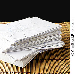 some stack of paper on the bamboo plate and black background