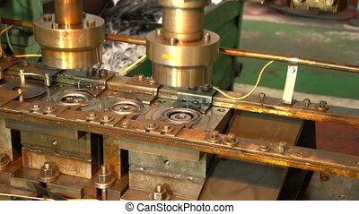Some tools of a forging machine make round metal items in a...