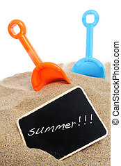 some toy shovels and a blackboard with the word summer written on it on the sand of a beach