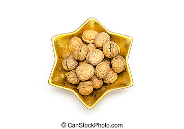 some walnuts in a golden star shaped bowl on a white background