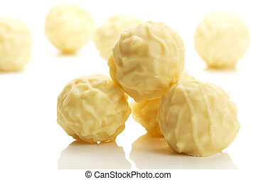 some yellow truffle pralines in front of others on white background