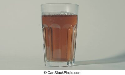 Somebody adding sugar into the glass of tea, then mixing it