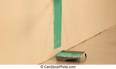 Somebody is painting wall in green color. Colorful...