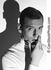 Thoughtful man in white polo neck with his hand on a chin