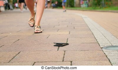 somebody loses his wallet that falls on the pavement in the...