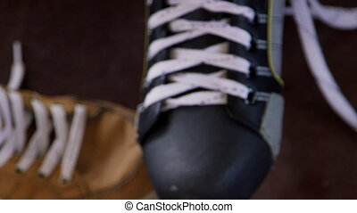 Somebody man hands laces black and grey skate for hockey.