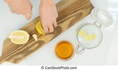 Someone cutting a lemon on the chopping board. top view -...