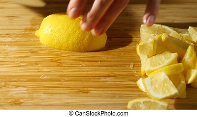 Someone cutting a lemon on the chopping board into small...