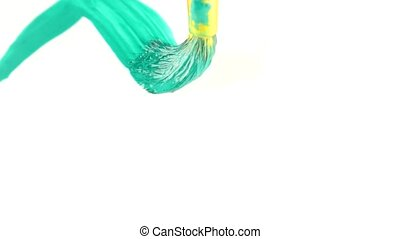 someone draws paint on a white sheet. close-up of a tassel....