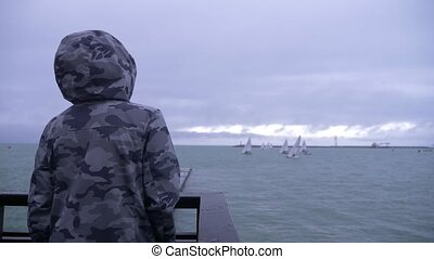 someone in a hooded jacket is standing on the pier and watching the sailboats sailing to the sea. 4k, slow motion.