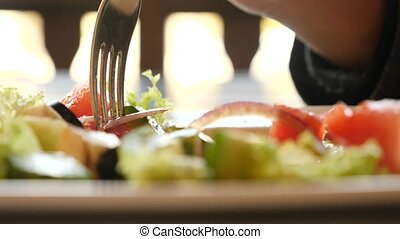 someone is eating a Greek salad in a fast food restaurant. 4k, slow-motion close-up