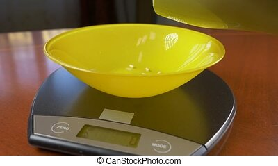 someone measures a piece of brown rice, on an electronic...