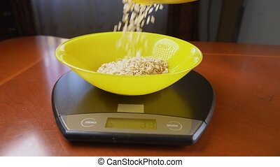 someone measures a piece of oatmeal, on an electronic scale...