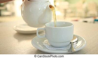 Someone pours tea from a porcelain white teapot into a white mug