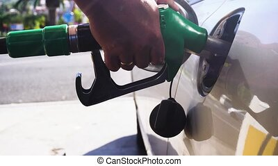 someone refueling car, close up scene on gasoline station