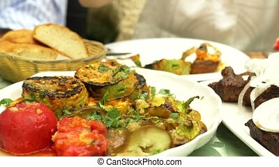 someone salting vegetables on a grill close-up in a restaurant. Woman salting grilled vegetables