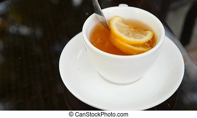 Someone stirs sugar with lemon in mug with green tea. 4k, slow motion.