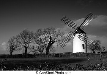 A black and white view of a windmill in Somerset, England.