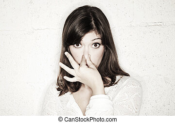 Portrait of a beautiful young woman staring into the camera with her eyes wide open and covering her nose with two fingers. Apparently something stinks.