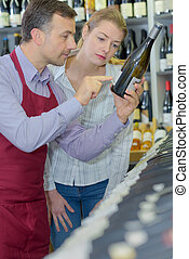 sommelier and female customer picking bottle of wine in store