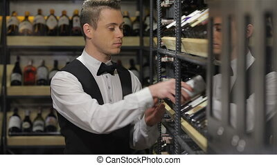Sommelier choosing a bottle of wine at the wine cellar. Sale...