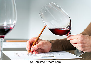Extreme close up of sommelier evaluating red wine in wine glass at tasting.
