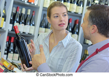 sommelier giving woman recommendation for bottle of wine