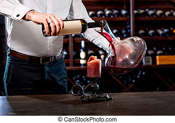 Sommelier in the wine cellar - Sommelier pouring wine to the...