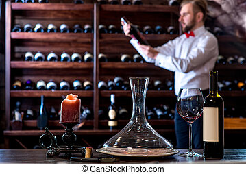 Sommelier in the wine cellar - Sommelier looking for good...