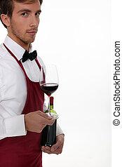 Sommelier serving a bottle of wine