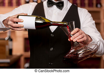 Sommelier with decanter. Cropped image of sommelier pouring wine to the decanter