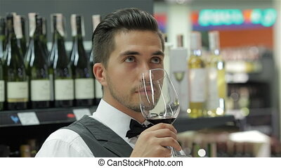 Sommelier with red wine and smelling it