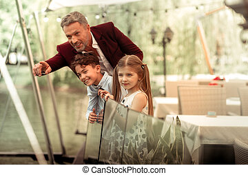 Excited cute son and daughter looking at ducks in lake with father