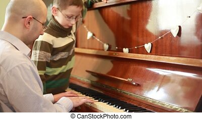 Son and father  in glasses playing piano