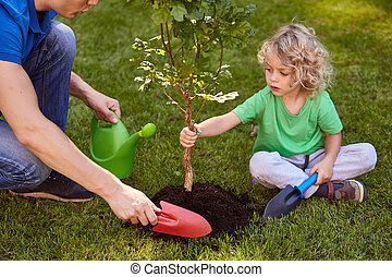 Son and father watering tree